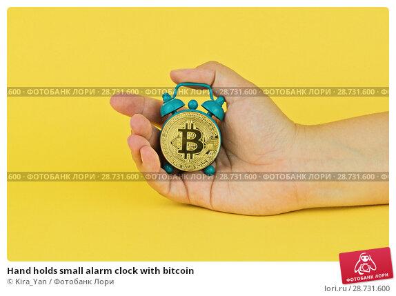 Купить «Hand holds small alarm clock with bitcoin», фото № 28731600, снято 6 июля 2018 г. (c) Kira_Yan / Фотобанк Лори