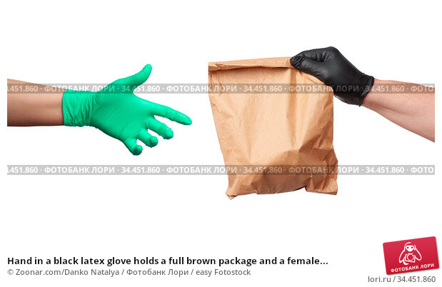 Hand in a black latex glove holds a full brown package and a female... Стоковое фото, фотограф Zoonar.com/Danko Natalya / easy Fotostock / Фотобанк Лори