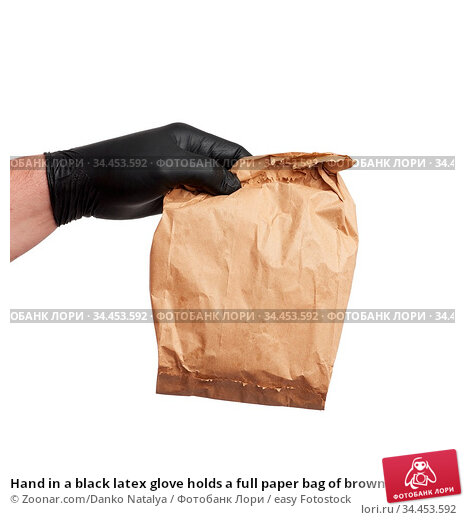 Hand in a black latex glove holds a full paper bag of brown craft... Стоковое фото, фотограф Zoonar.com/Danko Natalya / easy Fotostock / Фотобанк Лори