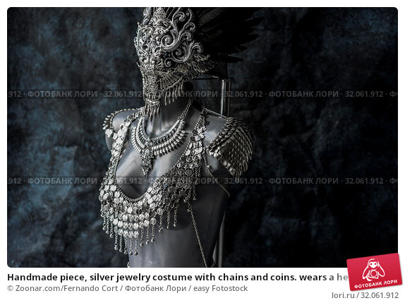 Handmade piece, silver jewelry costume with chains and coins. wears a headdress made with feathers and gothic pieces. Стоковое фото, фотограф Zoonar.com/Fernando Cort / easy Fotostock / Фотобанк Лори