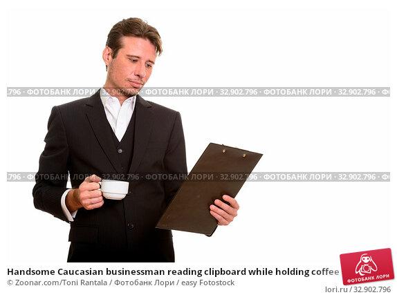 Handsome Caucasian businessman reading clipboard while holding coffee cup. Стоковое фото, фотограф Zoonar.com/Toni Rantala / easy Fotostock / Фотобанк Лори