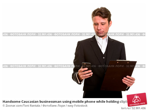 Handsome Caucasian businessman using mobile phone while holding clipboard. Стоковое фото, фотограф Zoonar.com/Toni Rantala / easy Fotostock / Фотобанк Лори