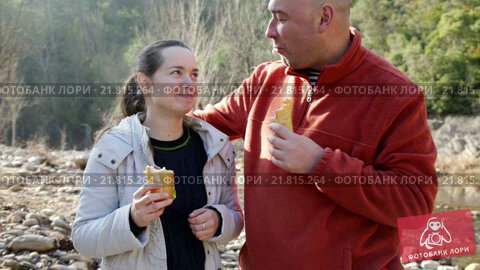 Купить «Handsome man and cheerful woman eating sandwitches at picnic outdoors», видеоролик № 21815264, снято 5 февраля 2016 г. (c) Яков Филимонов / Фотобанк Лори