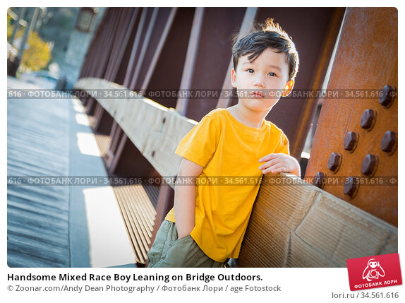 Handsome Mixed Race Boy Leaning on Bridge Outdoors. Стоковое фото, фотограф Zoonar.com/Andy Dean Photography / age Fotostock / Фотобанк Лори