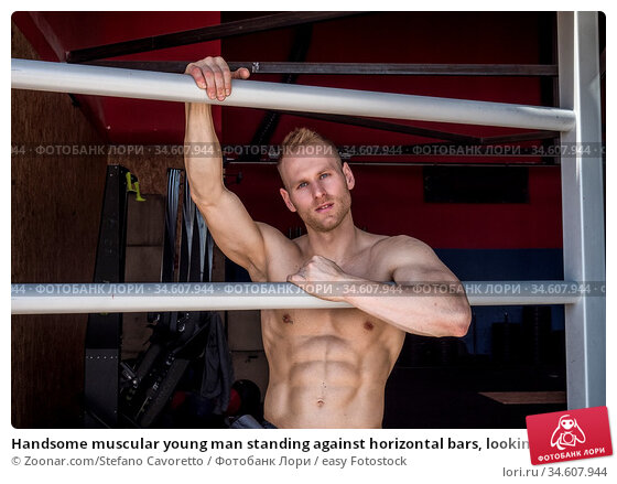 Handsome muscular young man standing against horizontal bars, looking... Стоковое фото, фотограф Zoonar.com/Stefano Cavoretto / easy Fotostock / Фотобанк Лори