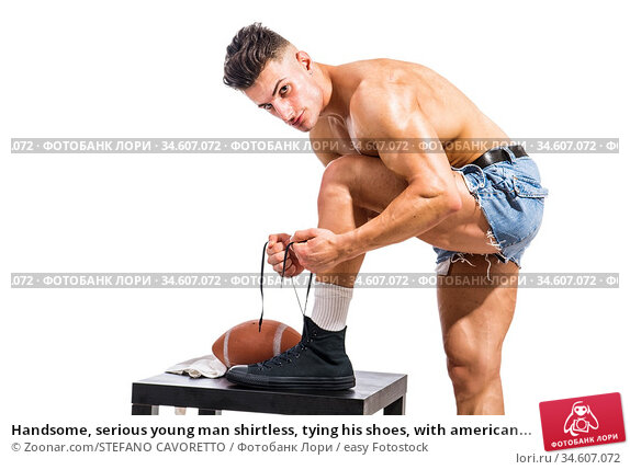 Handsome, serious young man shirtless, tying his shoes, with american... Стоковое фото, фотограф Zoonar.com/STEFANO CAVORETTO / easy Fotostock / Фотобанк Лори