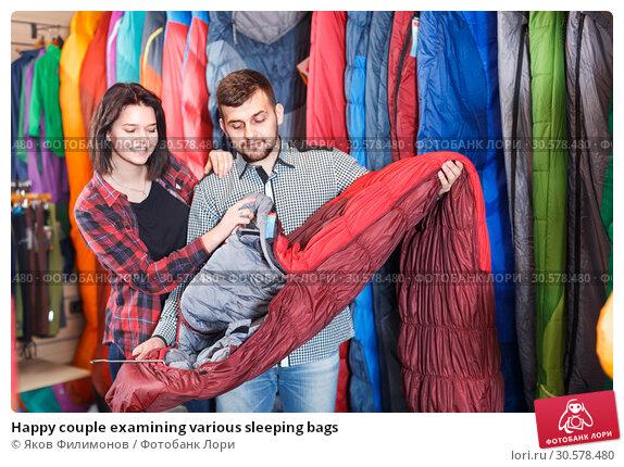 Купить «Happy couple examining various sleeping bags», фото № 30578480, снято 8 марта 2017 г. (c) Яков Филимонов / Фотобанк Лори