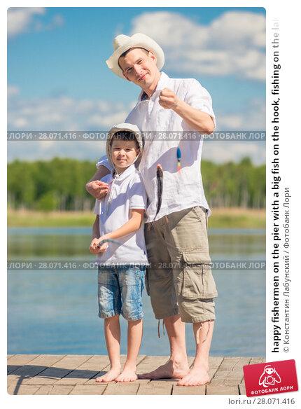 Купить «happy fishermen on the pier with a big fish on the hook, fishing on the lake», фото № 28071416, снято 14 июня 2016 г. (c) Константин Лабунский / Фотобанк Лори