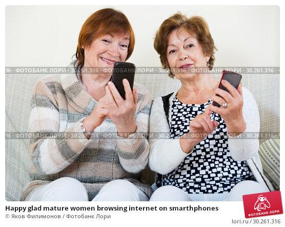 Купить «Happy glad mature women browsing internet on smarthphones», фото № 30261316, снято 23 июля 2019 г. (c) Яков Филимонов / Фотобанк Лори