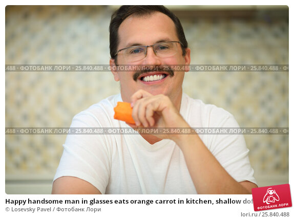 Купить «Happy handsome man in glasses eats orange carrot in kitchen, shallow dof», фото № 25840488, снято 2 сентября 2015 г. (c) Losevsky Pavel / Фотобанк Лори