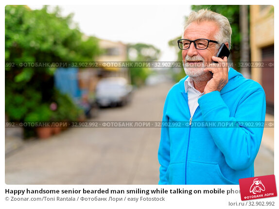 Happy handsome senior bearded man smiling while talking on mobile phone and thinking with eyeglasses outdoors. Стоковое фото, фотограф Zoonar.com/Toni Rantala / easy Fotostock / Фотобанк Лори