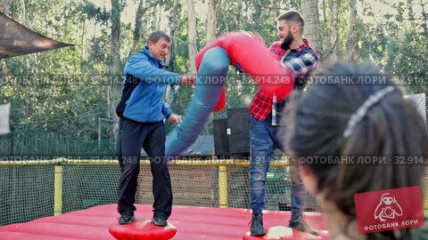 Happy male friends fighting by big stuffed boxing gloves at outdoor amusement playground. Стоковое видео, видеограф Яков Филимонов / Фотобанк Лори