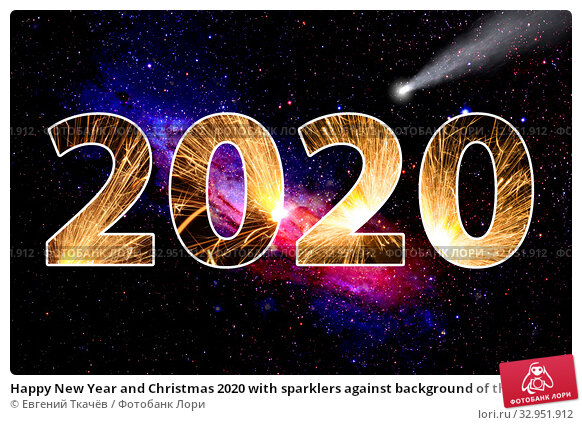 Happy New Year and Christmas 2020 with sparklers against background of the starry sky and galaxy. Стоковое фото, фотограф Евгений Ткачёв / Фотобанк Лори