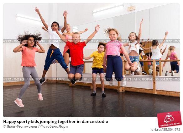 Happy sporty kids jumping together in dance studio. Стоковое фото, фотограф Яков Филимонов / Фотобанк Лори