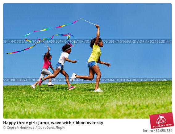 Happy three girls jump, wave with ribbon over sky. Стоковое фото, фотограф Сергей Новиков / Фотобанк Лори