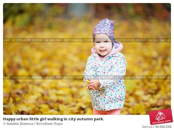 Happy urban little girl walking in city autumn park. Стоковое фото, фотограф Nataliia Zhekova / Фотобанк Лори