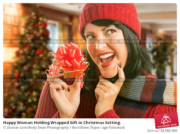 Happy Woman Holding Wrapped Gift in Christmas Setting. Стоковое фото, фотограф Zoonar.com/Andy Dean Photography / age Fotostock / Фотобанк Лори