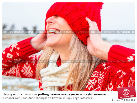 Happy woman in snow pulling beanie over eyes in a playful manner. Стоковое фото, фотограф Zoonar.com/Leah-Anne Thompson / age Fotostock / Фотобанк Лори