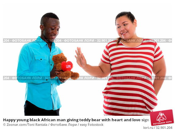 Happy young black African man giving teddy bear with heart and love sign to young fat Asian woman smiling and showing stop sign. Стоковое фото, фотограф Zoonar.com/Toni Rantala / easy Fotostock / Фотобанк Лори