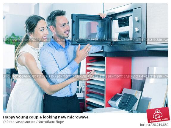 Купить «Happy young couple looking new microwave», фото № 28219880, снято 15 июня 2017 г. (c) Яков Филимонов / Фотобанк Лори