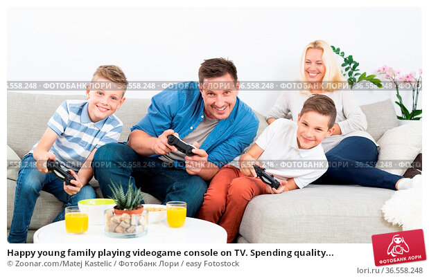 Happy young family playing videogame console on TV. Spending quality... Стоковое фото, фотограф Zoonar.com/Matej Kastelic / easy Fotostock / Фотобанк Лори