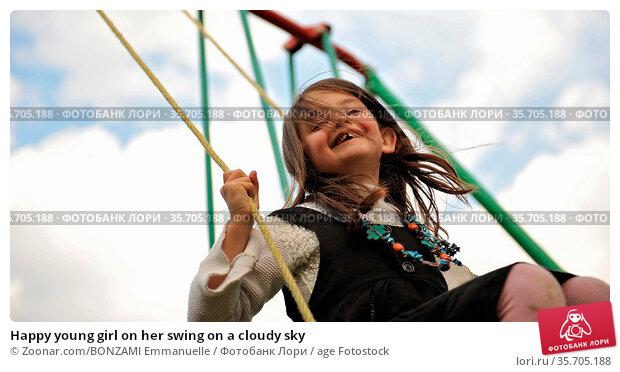 Happy young girl on her swing on a cloudy sky. Стоковое фото, фотограф Zoonar.com/BONZAMI Emmanuelle / age Fotostock / Фотобанк Лори