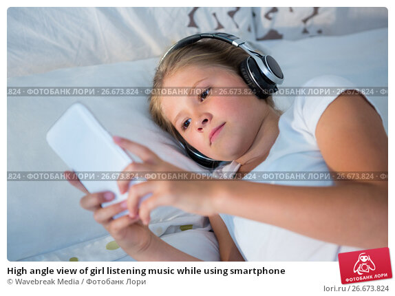 Купить «High angle view of girl listening music while using smartphone», фото № 26673824, снято 26 января 2017 г. (c) Wavebreak Media / Фотобанк Лори
