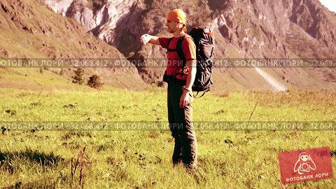 Hiking man walking on green mountain meadow with backpack. Summer sport and recreation concept. Стоковое видео, видеограф Александр Маркин / Фотобанк Лори