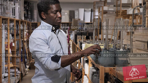 Interested african american man visiting store of household goods in search of new bathroom accessories. Стоковое видео, видеограф Яков Филимонов / Фотобанк Лори