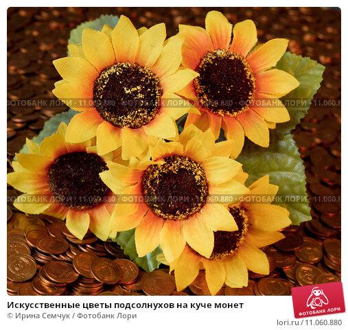 Искусственные цветы подсолнухов на куче монет. Стоковое фото, фотограф Ирина Семчук / Фотобанк Лори