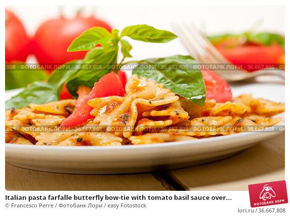 Italian pasta farfalle butterfly bow-tie with tomato basil sauce over... Стоковое фото, фотограф Francesco Perre / easy Fotostock / Фотобанк Лори