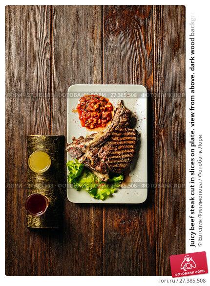 Купить «Juicy beef steak cut in slices on plate. view from above. dark wood background.», фото № 27385508, снято 11 ноября 2016 г. (c) Евгения Филимонова / Фотобанк Лори