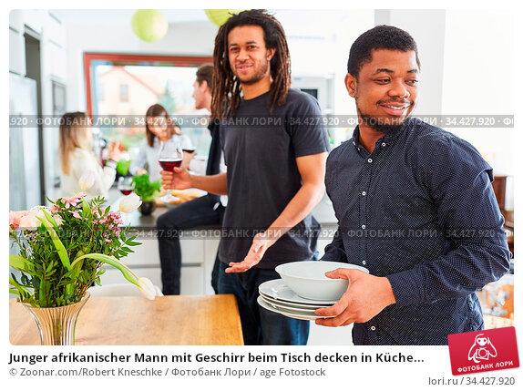 Junger afrikanischer Mann mit Geschirr beim Tisch decken in Küche... Стоковое фото, фотограф Zoonar.com/Robert Kneschke / age Fotostock / Фотобанк Лори