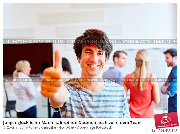 Junger glücklicher Mann hält seinen Daumen hoch vor einem Team. Стоковое фото, фотограф Zoonar.com/Robert Kneschke / age Fotostock / Фотобанк Лори
