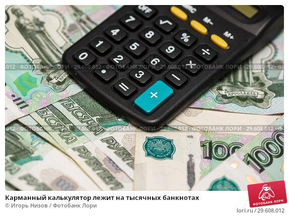 Купить «Карманный калькулятор лежит на тысячных банкнотах», фото № 29608012, снято 19 декабря 2018 г. (c) Игорь Низов / Фотобанк Лори