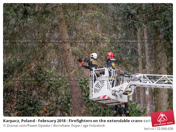 Karpacz, Poland - February 2018 : Firefighters on the extendable crane cutting branches of a tree for safety reasons after heavy snowfall. Стоковое фото, фотограф Zoonar.com/Pawel Opaska / age Fotostock / Фотобанк Лори
