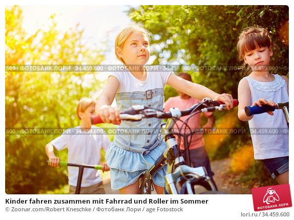 Kinder fahren zusammen mit Fahrrad und Roller im Sommer. Стоковое фото, фотограф Zoonar.com/Robert Kneschke / age Fotostock / Фотобанк Лори