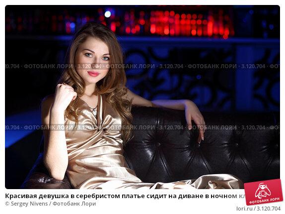 4be2c9bac39 Купить «Красивая девушка в серебристом платье сидит на диване в ночном клубе»