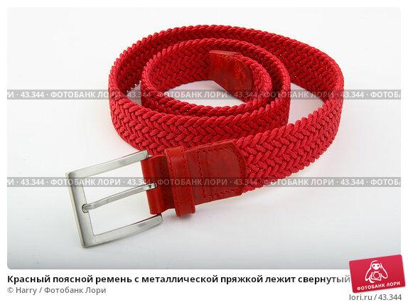 Красный поясной ремень с металлической пряжкой лежит свернутый на белом фоне, фото № 43344, снято 24 марта 2005 г. (c) Harry / Фотобанк Лори