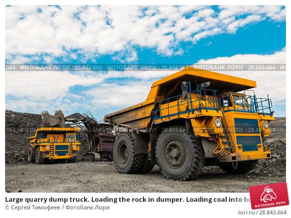 Купить «Large quarry dump truck. Loading the rock in dumper. Loading coal into body truck. Production useful minerals. Mining truck mining machinery, to transport coal from open-pit as the coal production.», фото № 28843664, снято 22 июня 2018 г. (c) Сергей Тимофеев / Фотобанк Лори