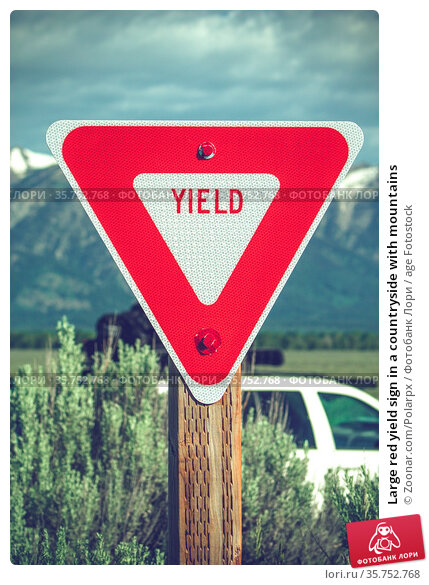 Large red yield sign in a countryside with mountains. Стоковое фото, фотограф Zoonar.com/Polarpx / age Fotostock / Фотобанк Лори