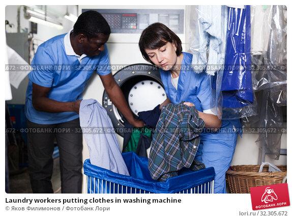 Купить «Laundry workers putting clothes in washing machine», фото № 32305672, снято 15 января 2019 г. (c) Яков Филимонов / Фотобанк Лори