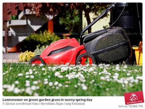 Lawnmower on green garden grass in sunny spring day. Стоковое фото, фотограф Zoonar.com/Artush Foto / easy Fotostock / Фотобанк Лори