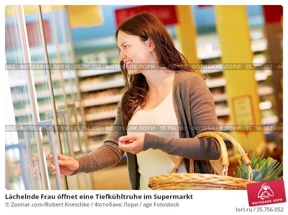 Lächelnde Frau öffnet eine Tiefkühltruhe im Supermarkt. Стоковое фото, фотограф Zoonar.com/Robert Kneschke / age Fotostock / Фотобанк Лори