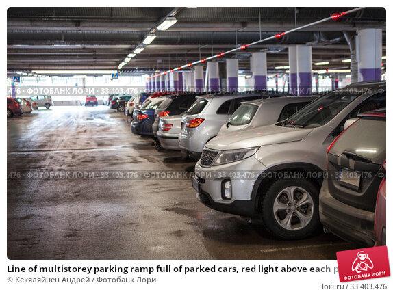 Купить «Line of multistorey parking ramp full of parked cars, red light above each place», фото № 33403476, снято 5 апреля 2018 г. (c) Кекяляйнен Андрей / Фотобанк Лори