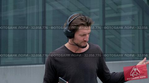 Listening music Freelancer Man in the big urban city working with a laptop phone camera and headphones. Стоковое видео, видеограф Aleksejs Bergmanis / Фотобанк Лори