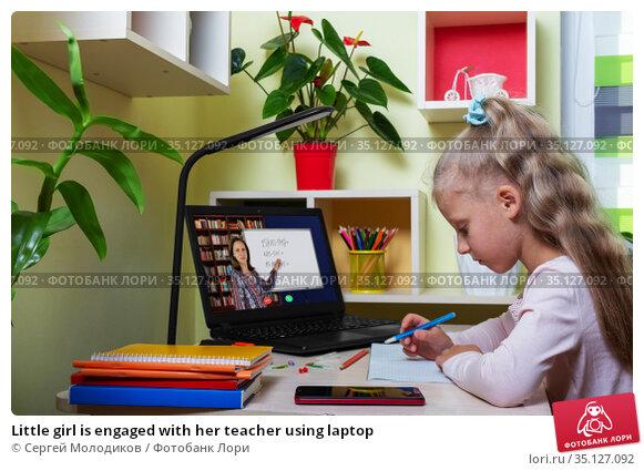 Little girl is engaged with her teacher using laptop. Стоковое фото, фотограф Сергей Молодиков / Фотобанк Лори