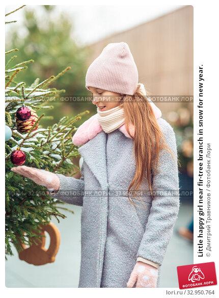Little happy girl near fir-tree branch in snow for new year. Стоковое фото, фотограф Дмитрий Травников / Фотобанк Лори