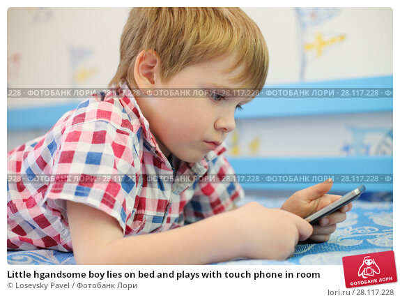 Купить «Little hgandsome boy lies on bed and plays with touch phone in room», фото № 28117228, снято 7 мая 2016 г. (c) Losevsky Pavel / Фотобанк Лори