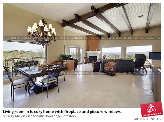 Living room in luxury home with fireplace and picture windows. Редакционное фото, фотограф Larry Malvin / age Fotostock / Фотобанк Лори